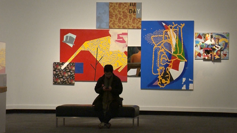 A visitor to the Glenbow Museum seated in front of an art installation