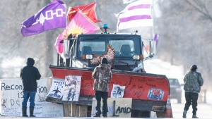 Protesters look at signatures written on the blade of a snowplow parked adjacent to the closed rail line near Belleville, Ont., on Thursday Feb. 20, 2020, in Tyendinaga Mohawk Territory, on Friday, Feb. 21, 2020, as they stand in solidarity with the Wet'suwet'en hereditary chiefs opposed to the Coastal GasLink pipeline in northern British Columbia. THE CANADIAN PRESS/Justin Tang