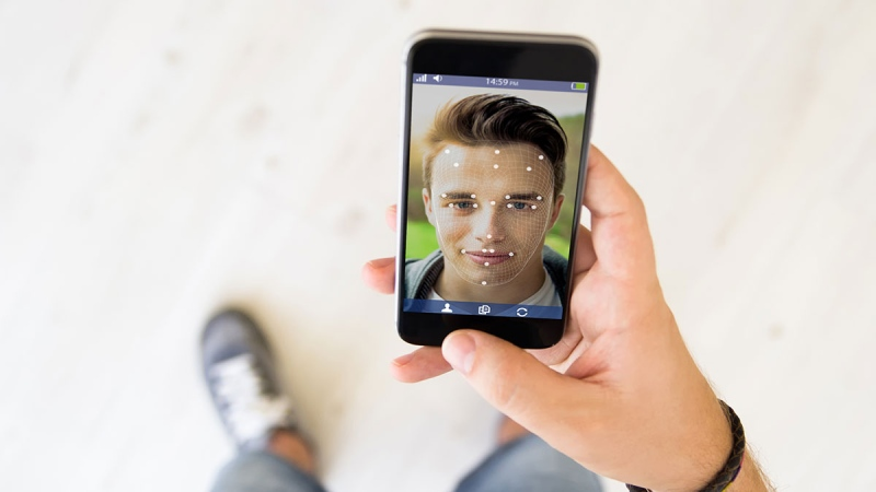 A man uses facial-recognition software in this photo from shutterstock.com