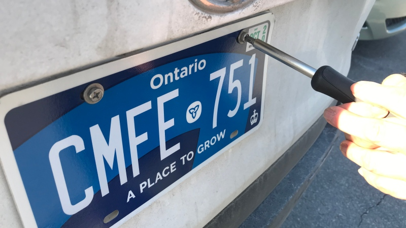 Asad Abbas puts on his new licence plates at a Service Ontario location. (Craig Wadman/CTV News Toronto)