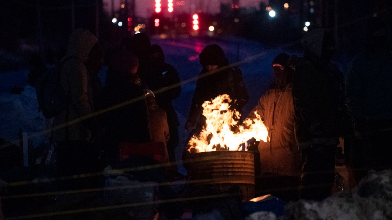 Protesters keep warm around a fire at a rail blockade in Saint-Lambert, Que. on Friday, February 21, 2020. The protesters are blocking the line in solidarity with the Wet'suwet'en hereditary chiefs opposed to the LNG pipeline in northern British Columbia. THE CANADIAN PRESS/Paul Chiasson