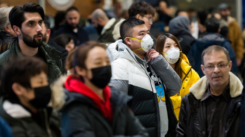 People wear masks as they wait for the arrivals at the International terminal at Toronto Pearson International Airport in Toronto on Saturday, January 25, 2020. THE CANADIAN PRESS/Nathan Denette