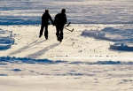 A pair of hockey players skating on a frozen lake