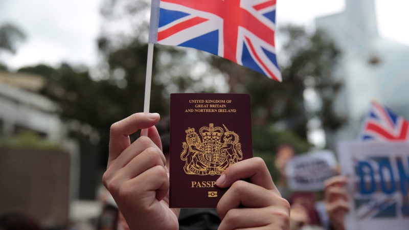 A protestor holds up his British passport and participates in a peaceful demonstration outside the British Consulate in Hong Kong, Sunday, Sept. 1, 2019. (AP Photo/Jae C. Hong)