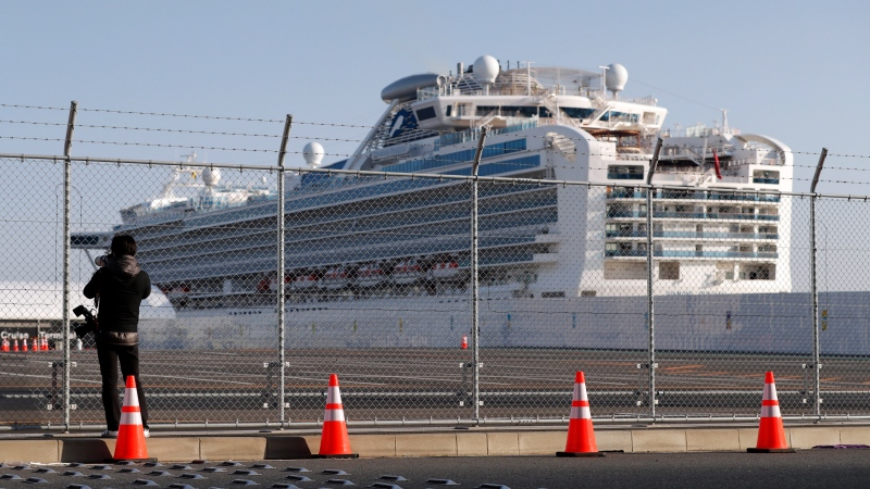 A photographer takes photos near the quarantined Diamond Princess cruise ship anchored at a port in Yokohama, near Tokyo, Friday, Feb. 21, 2020. (AP Photo/Eugene Hoshiko)
