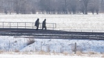 Two people walk on the closed train tracks in Tyendinaga, near Belleville, Ont., on Saturday Feb.22, 2020, near a rail blockade in support of the Wet'suwet'en who oppose work on a pipeline in northern B.C. THE CANADIAN PRESS/Lars Hagberg