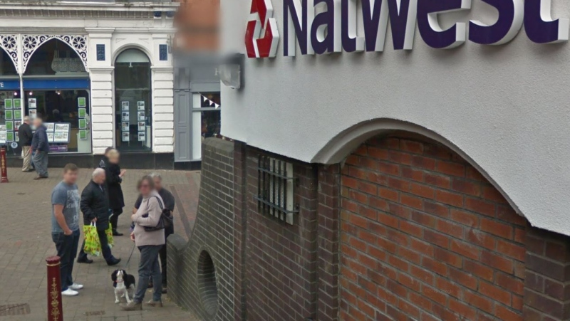 A screengrab from Google Streetview showing a hole in a wall, bottom left, outside a NatWest bank in the town of Ilkeston in England. (Google Streetview)