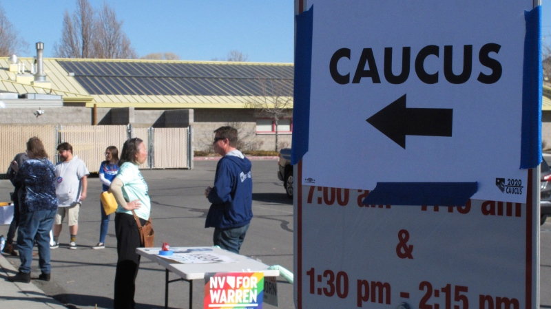 Volunteers for various campaigns talk to voters as they enter a presidential caucus site at Mendive Middle School in Sparks, Nev., on Saturday, Feb. 22, 2020. (AP Photo/Scott Sonner)