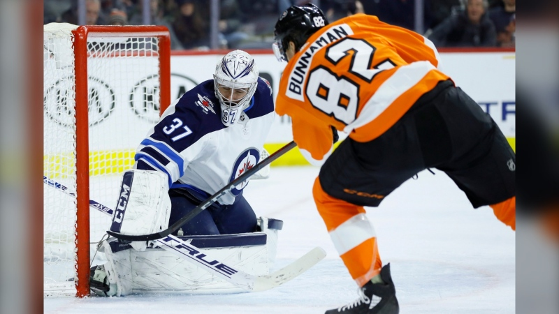 Winnipeg Jets' Connor Hellebuyck (37) blocks a shot by Philadelphia Flyers' Connor Bunnaman (82) during the second period of an NHL hockey game, Saturday, Feb. 22, 2020, in Philadelphia. (AP Photo/Matt Slocum)