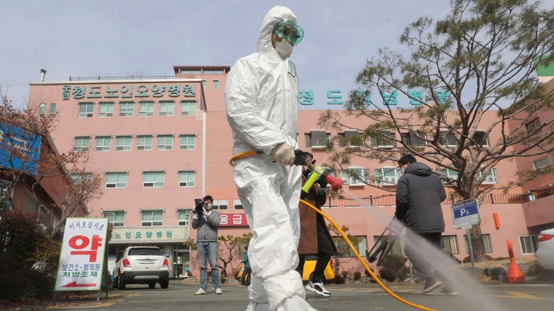 "A worker wearing protective gears sprays disinfectant against the coronavirus in front of the Daenam Hospital in Cheongdo, South Korea, Friday, Feb. 21, 2020. South Korea on Friday declared a ""special management zone"" around a southeastern city where a surging viral outbreak, largely linked to a church in Daegu, threatens to overwhelm the region's health system. (Lim Hwa-young/Yonhap via AP)"