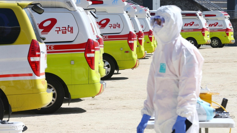 Ambulances gather as a member of paramedic wearing protective gears walk in Daegu, South Korea, Sunday, Feb. 23, 2020. (Kim Hyun-tai/Yonhap via AP)