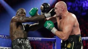 Tyson Fury, right, of England, hits Deontay Wilder during a WBC heavyweight championship boxing match Saturday, Feb. 22, 2020, in Las Vegas. (AP Photo/Isaac Brekken)