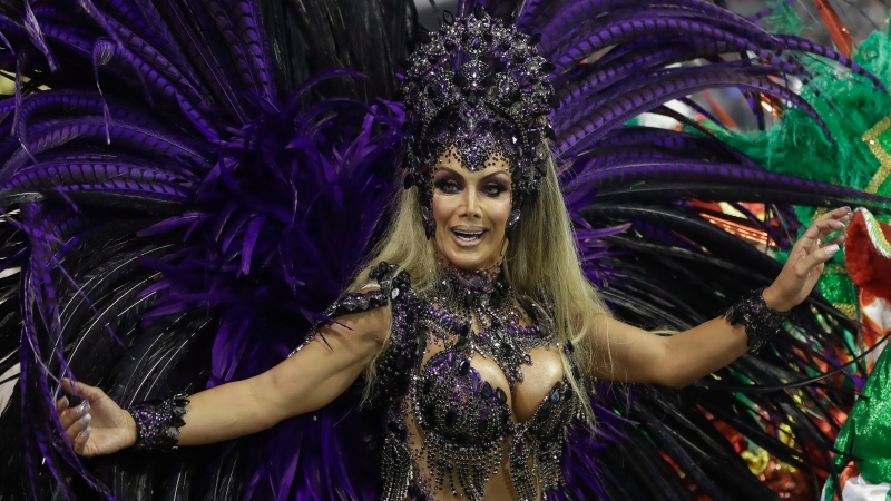 Transgender godmother Camila Prins, representing the Colorado do Bras samba school, performs at Carnival in the Sambadrome in Sao Paulo, Brazil, Saturday, Feb. 22, 2020. Prins entered the parade grounds, in a costume of feathers that displayed her sinuous body, fulfilling a dream nearly three decades old. (AP Photo/Andre Penner)