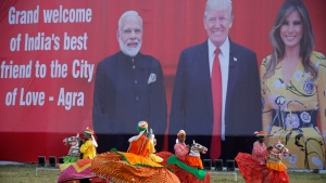 Indian folk dancers rehearse their performance next to a billboard featuring Indian Prime Minister Narendra Modi, U.S. President Donald Trump and first lady Melania Trump at the airport in Agra, India, Sunday, Feb. 23, 2020. Trump on Monday is expected to travel to Agra to visit the 17th century monument to love, the Taj Mahal. (AP Photo/Rajesh Kumar Singh)