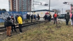 Video from the scene showed a small group of people had gathered at the rail crossing at Glen Drive, near Venables Street. Protesters were not blocking the road, only the railway. (Allison Hurst/CTV)