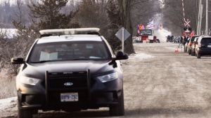 An OPP cruiser and two officers sit parked a short distance from the closed train tracks in Tyendinaga, near Belleville, Ont., on Sunday, Feb.23, 2020. Protesters have blockaded the railway tracks in support of the Wet'suwet'en who oppose work on a pipeline in northern B.C. Media work at right. THE CANADIAN PRESS/Sean Kilpatrick