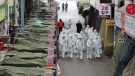 Workers wearing protective gear spray disinfectant as a precaution against the COVID-19 coronavirus in a local market in Daegu, South Korea, Sunday, Feb. 23, 2020.  (Im Hwa-young/Yonhap via AP)