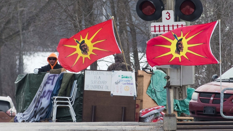 People stand near the blockaded train tracks in Tyendinaga, near Belleville, Ont., on Sunday Feb. 23, 2020. The protest is in support of the Wet'suwet'en hereditary chiefs, who oppose a pipeline project in northern B.C. THE CANADIAN PRESS/Lars Hagberg