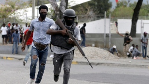 Off-duty police officers run towards and armed clash with army soldiers during a protest over police pay and working conditions, in Port-au-Prince, Haiti, Sunday, Feb. 23, 2020. (AP Photo/Dieu Nalio Chery)