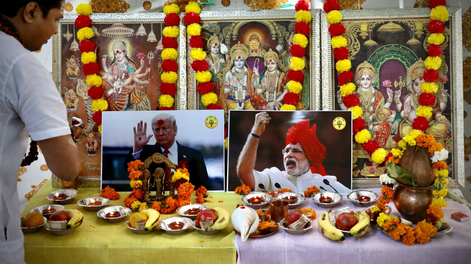 A Hindu priest performs prayers in front of portraits of Indian Prime Minister Narendra Modi and U.S. President Donald Trump leaning on portraits of Hindu gods and goddesses in New Delhi, India, Monday, Feb. 24, 2020. (AP Photo/Manish Swarup)