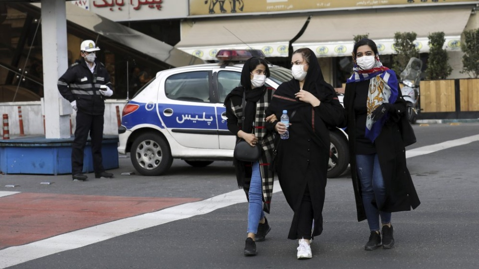 A policeman and pedestrians wear masks to help guard against the Coronavirus, in downtown Tehran, Iran, Sunday, Feb. 23, 2020. (AP Photo/Ebrahim Noroozi)
