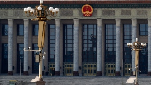 In this Sunday, Feb. 23, 2020, photo, a paramilitary policeman stands guard on a deserted Tiananmen Square against the Great Hall of the People in Beijing. (AP Photo/Andy Wong)