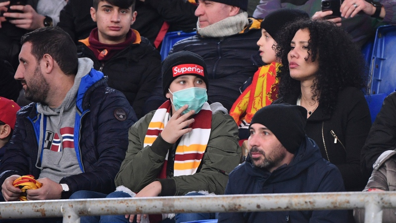 An AS Roma fan wears a sanitary mask as he watches the Italian Serie A soccer match between Roma and Lecce at the Olympic stadium in Rome, Sunday, Feb. 23, 2020. (Alfredo Falcone/LaPresse via AP)
