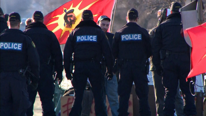 Police officers face off with protesters at a rail blockade in Tyendinaga, Ont. on Monday, Feb. 24, 2020.