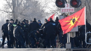 Ontario Provincial Police officers make an arrest at a rail blockade in Tyendinaga Mohawk Territory, near Belleville, Ont., on Monday Feb. 24, 2020. THE CANADIAN PRESS/Adrian Wyld