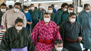 In this Sunday, Feb. 23, 2020, photo, sumo wrestlers wearing masks arrive at Shin Osaka railway station in Osaka, western Japan. (Kyodo News via AP)