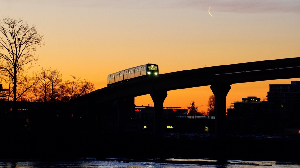 A Canada Line train passes a waning moon in Richmond, B.C., on Feb. 20, 2020. (Lay Tan / Weather Watch by CTV Vancouver)