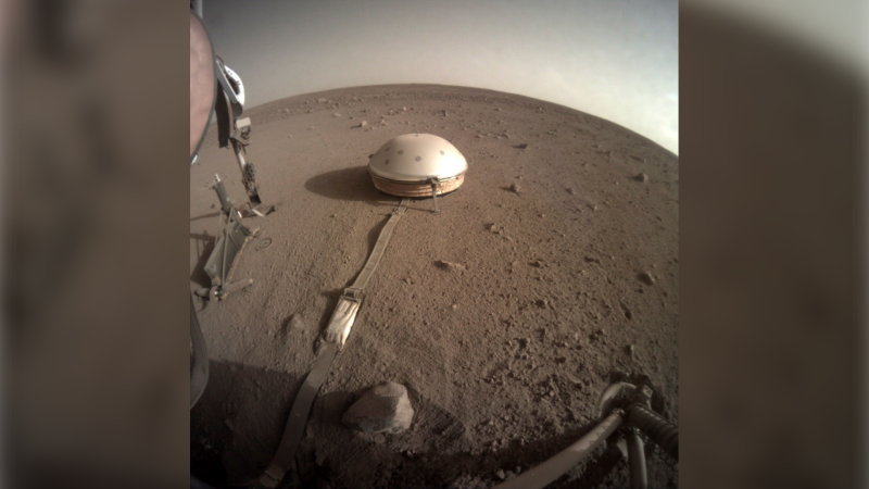 This Feb. 18, 2020 photo made available by NASA shows the InSight lander's dome-covered seismometer, known as SEIS, on Mars. On Monday, Feb. 24, 2020, scientists reported that the spacecraft has detected hundreds of quakes and even aftershocks that are regularly jolting the red planet. (NASA/JPL-Caltech via AP)