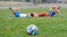 Kids lying down on a soccer field (Pexels)