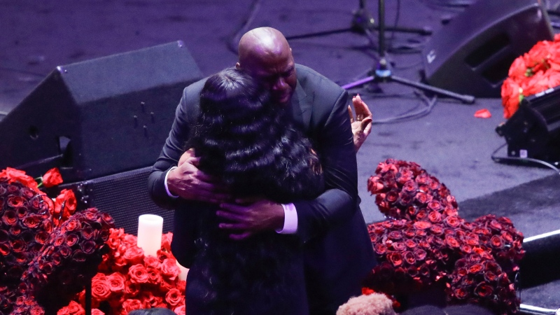 Former Los Angeles Lakers' Magic Johnson hugs Pam Bryant mother of Kobe Bryant during a celebration of life for Kobe Bryant and his daughter Gianna Monday, Feb. 24, 2020, in Los Angeles. (AP Photo/Marcio Jose Sanchez)