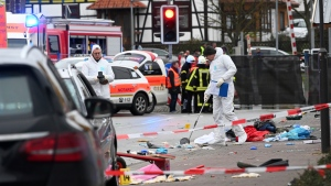 Police and rescue workers stand next to the scene of the accident with a car that is said to have crashed into a carnival parade in Volkmarsen, central Germany, Monday, Feb. 24, 2020. (Uwe Zucchi/dpa via AP)