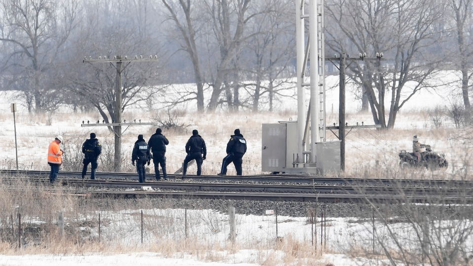 Ontario Provincial Police keep their eye on a Mohawk protester on an ATV while CN rail workers inspect the line as they prepare to resume service after arrests were made at a rail blockade in Tyendinaga Mohawk Territory, near Belleville, Ont., on Monday Feb. 24, 2020. THE CANADIAN PRESS/Adrian Wyld