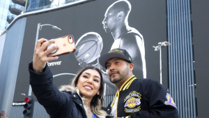 Alyssa Quevedo and her husband Emmanuel take a selfie in front of a mural of Kobe Bryant near the Staples Center before a public memorial for former Los Angeles Lakers star Kobe Bryant and his daughter, Gianna, in Los Angeles, Monday, Feb. 24, 2020. (AP Photo/Ringo H.W. Chiu)