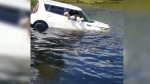Shawn Turner is seen jumping into the white vehicle after it crashed into a canal in Florida. (Shawn Turner via Storyful)