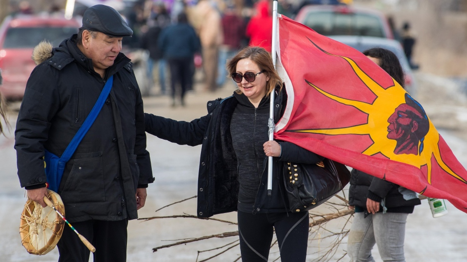 A woman walks with a Mohawk flag in Tyendinaga Mohawk Territory, near Belleville, Ont., on Monday Feb. 24, 2020, during a protest in solidarity with Wet'suwet'en Nation hereditary chiefs attempting to halt construction of a natural gas pipeline on their traditional territories. THE CANADIAN PRESS/Lars Hagberg