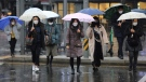 People wearing face masks walk on a street in Seoul, South Korea, Tuesday, Feb. 25, 2020. (AP Photo/Ahn Young-joon)