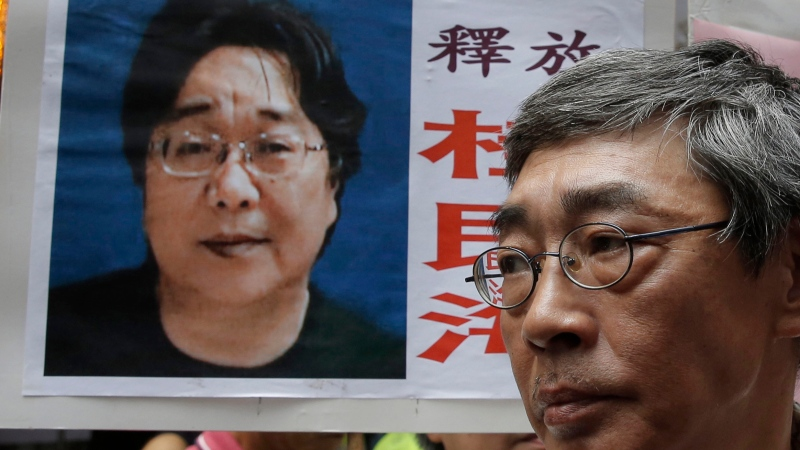 FILE - In this June 18, 2016, file photo, a picture of missing bookseller Gui Minhai is shown on a placard beside freed Hong Kong bookseller Lam Wing-kee, as the protesters are marching to the Chinese central government's liaison office in Hong Kong. (AP Photo/Kin Cheung, File)