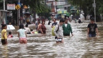Indonesians wade through flood water on a street in Jakarta, Indonesia, Tuesday, Feb. 25, 2020. (AP Photo/Tatan Syuflana)