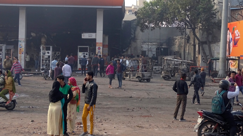 People stand by a gasoline station that was set on fire Monday in New Delhi, India, Tuesday, Feb. 25, 2020. (AP Photo/Dinesh Joshi)