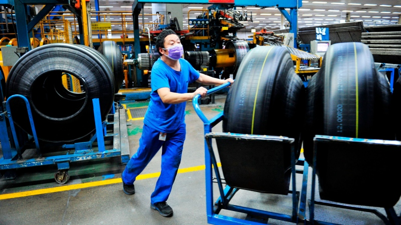 In this Monday, Feb. 24, 2020, photo, a worker wears a mask as he pushes a trolley of tires manufactured at a factory in Qingdao in eastern China's Shandong province. (Chinatopix via AP)