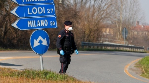 A Carabinieri (Italian paramilitary police) officer checks transit to or from the cordoned area in Codogno, some 50 kilometers South-East of Milan, Italy, Monday, Feb. 24, 2020. (AP Photo/Antonio Calanni)