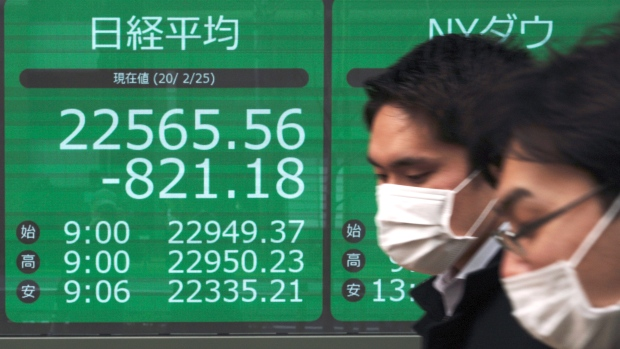 Men walk past an electronic stock board showing Japan's Nikkei 225 index at a securities firm in Tokyo Tuesday, Feb. 25, 2020. Shares are mostly lower in Asia on Tuesday after Wall Street suffered its worst session in two years, with the Dow Jones Industrial Average slumping more than 1,000 points on fears that a viral outbreak that began in China will weaken the world economy. (AP Photo/Eugene Hoshiko)