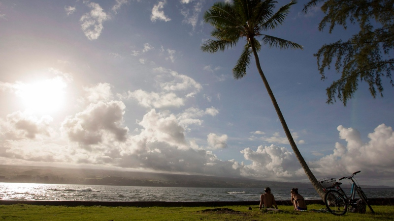 In this Aug. 30, 2015, file photo, Keenin Ide, left, of Hilo, Hawaii, and Medea Yankova, of Sofia, Bulgaria, sit near Hilo Bay in Hilo, Hawaii. (AP Photo/Caleb Jones, File)