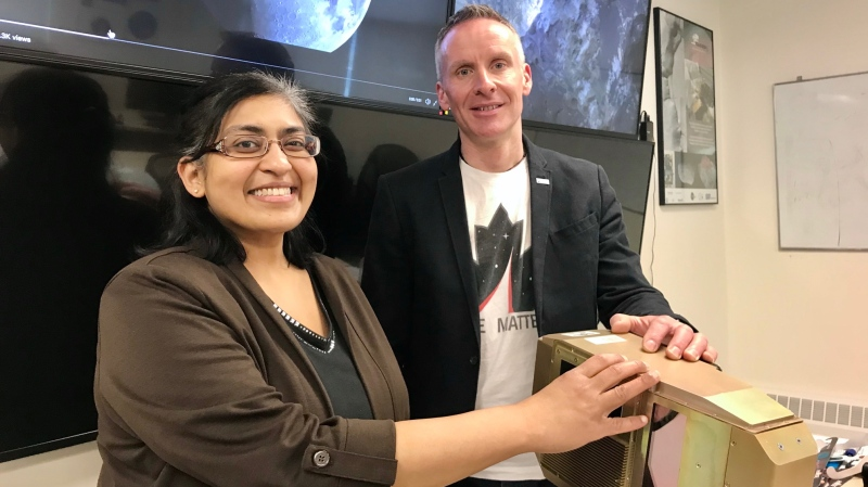 Jayshri Sabarinathan and Gordon Ozinski of Western Space pose with an earlier example of an Integrated Vision System in London, Ont. on Tuesday, Feb. 25, 2020. They'll lead a team developing a modern version for the next moon landing. (Sean Irvine / CTV London)