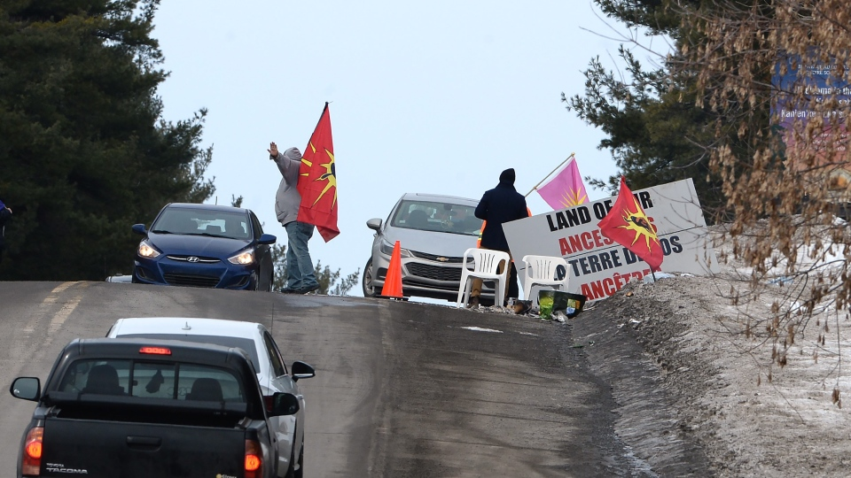 Protesters let vehicles past a check point on a highway in Kanesatake Mohawk Territory, near Oka, Que. on Tuesday, Feb. 25, 2020, as they protest in solidarity with Wet'suwet'en Nation hereditary chiefs attempting to halt construction of a natural gas pipeline on their traditional territories. THE CANADIAN PRESS/Ryan Remiorz