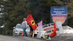 Protesters man a check point on a highway in Kanesatake Mohawk Territory, near Oka, Que. on Tuesday, Feb. 25, 2020, as they protest in solidarity with Wet'suwet'en Nation hereditary chiefs attempting to halt construction of a natural gas pipeline on their traditional territories. THE CANADIAN PRESS/Ryan Remiorz
